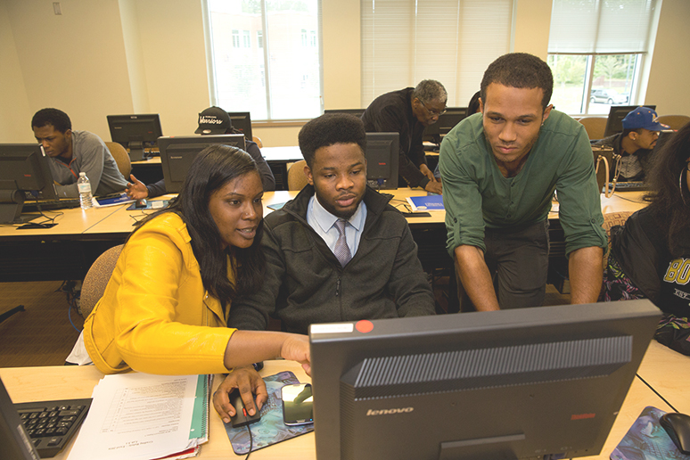 One female and two male students huddle around a computer screen