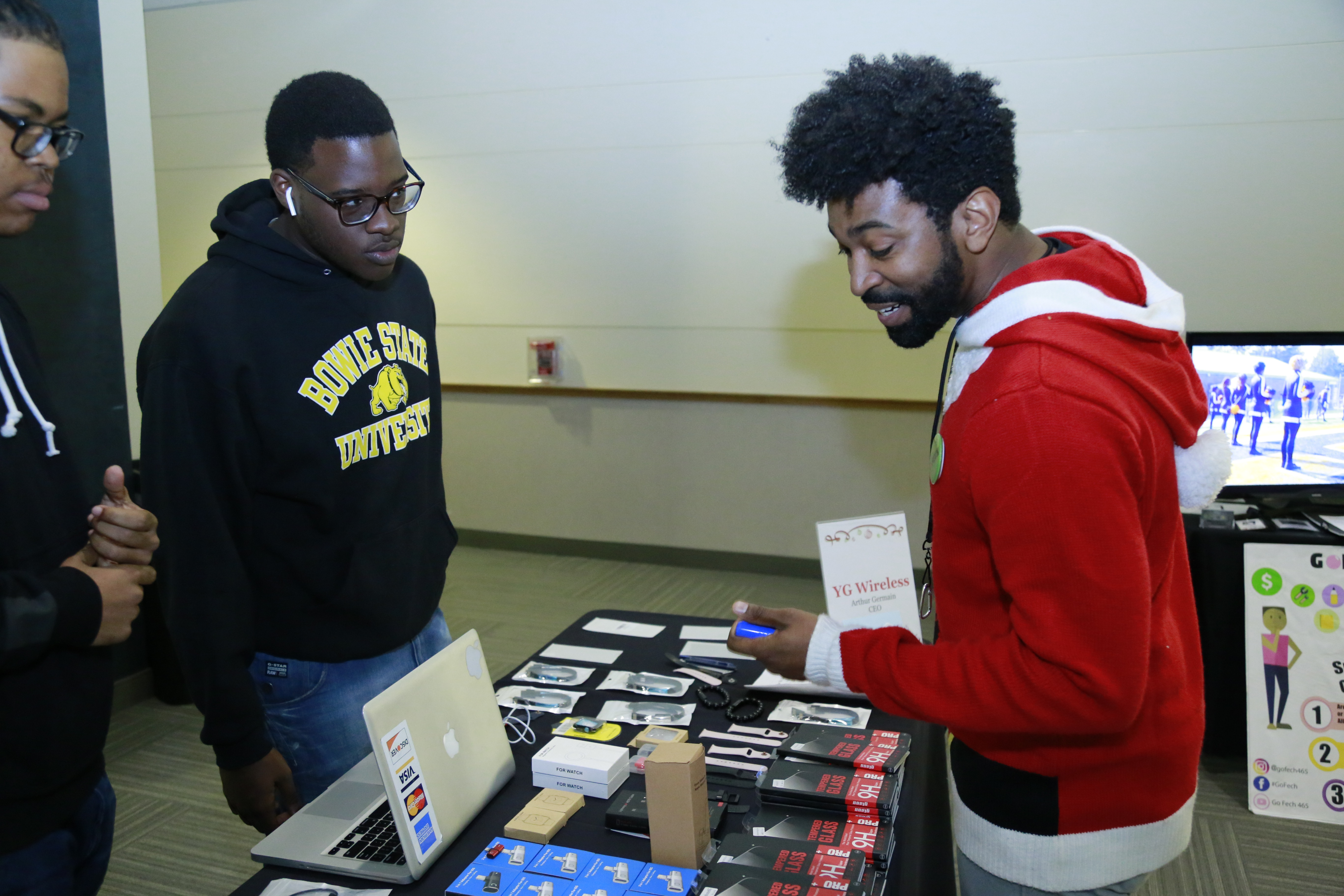 Male student showcases items for sale on a table to another male student