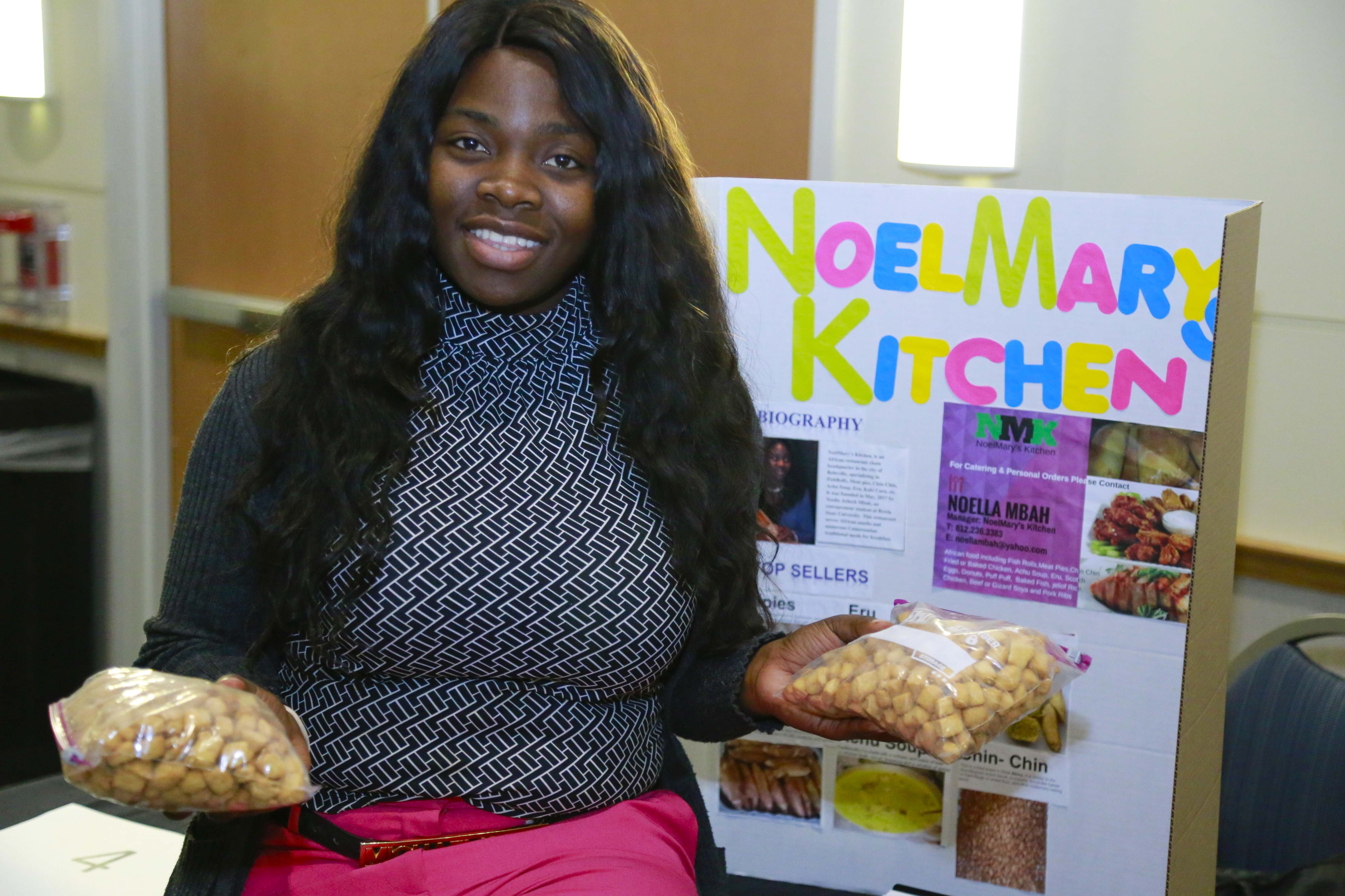 Female student holds bags of pre-packaged foods, while she sits on a table with a poster board describing her business