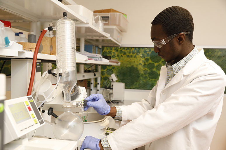 Christ Tessofo wears a white lab coat and works with a large device in a lab
