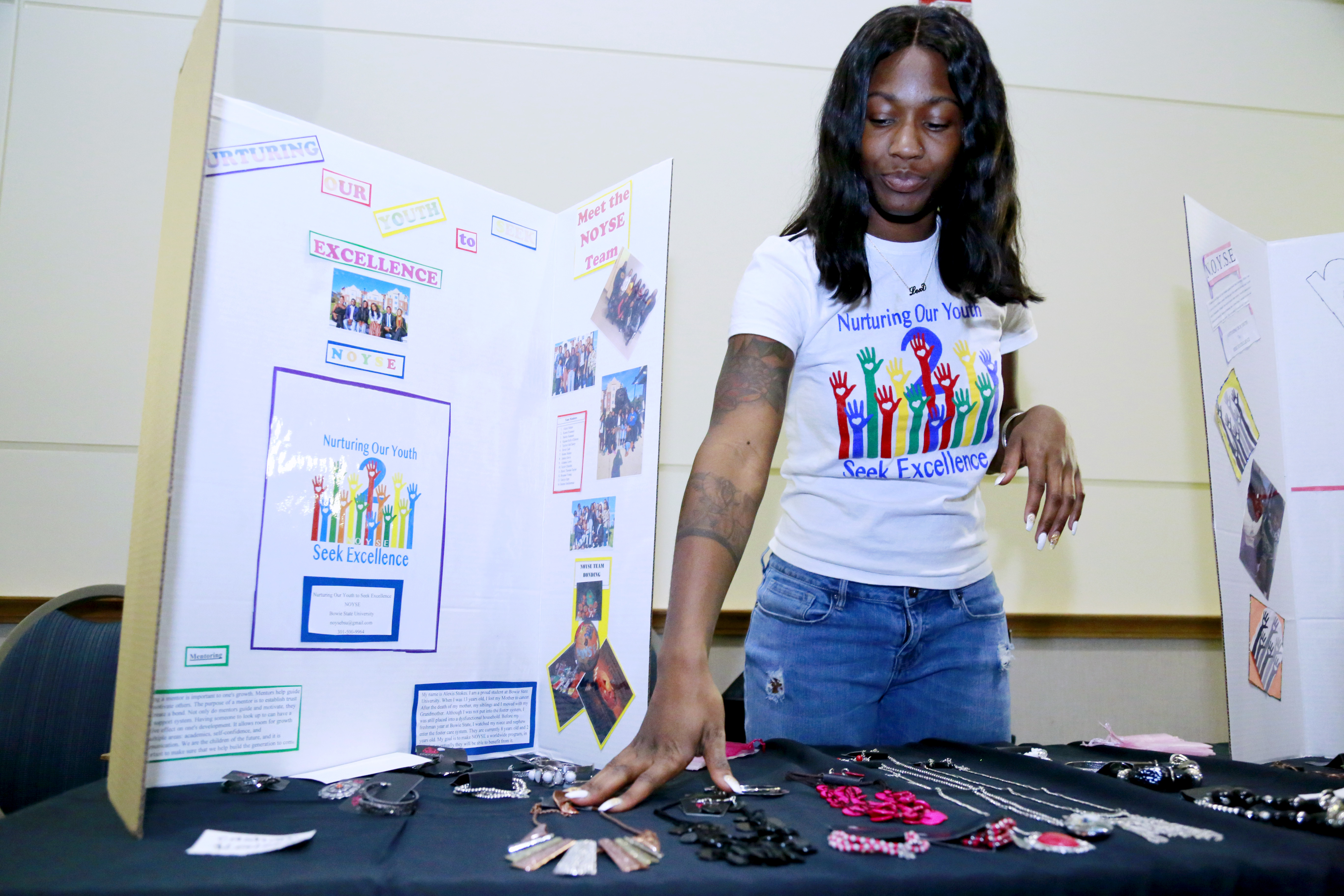 Female student displays jewelry for sale on a table, with a poster board describing her business