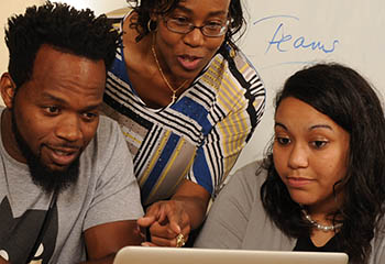 Professor Rochelle Daniel works with a male student and a female student on a laptop