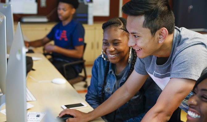 Students are laughing as they huddle around a computer